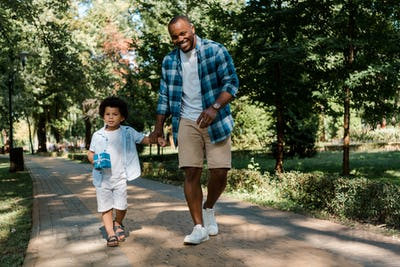 happy african american father holding hands with son while walking on path in park