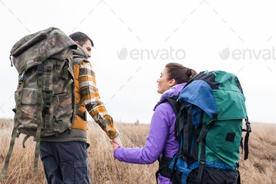 Back view of young smiling couple with backpacks holding hands and walking in tall grass in rural
