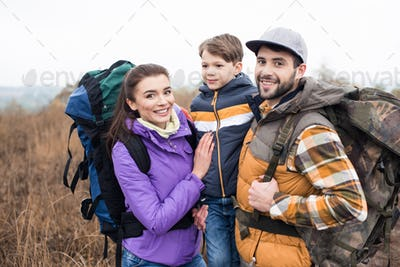 Close-up portrait of smiling family with backpacks standing embracing on rural path