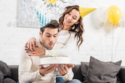 man blowing out candles on birthday cake with smiling woman in party hat on background