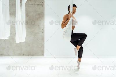 Beautiful relaxed girl in hammock practicing antigravity yoga in light studio