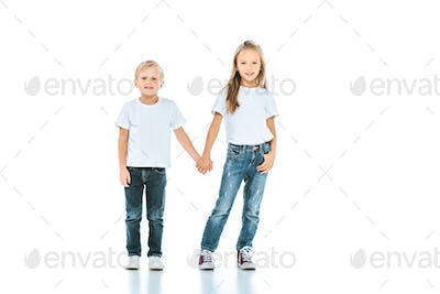 cute kids holding hands and standing in blue jeans on white