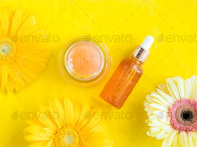 Vitamin C serum and cream with yellow beautiful flower on monochrome background in water with ripple