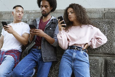 Bottom view of three young people standing with mobile phones