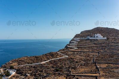 Folegandros island, Greece, Cyclades. Panagia Virgin Mary Church and long zigzag road.