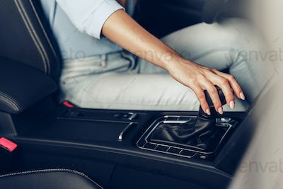 Female hand on gear lever in a car