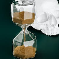 Gold hourglass and fake skull on dark green background