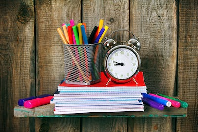 Writing-books, an alarm clock and school tools.