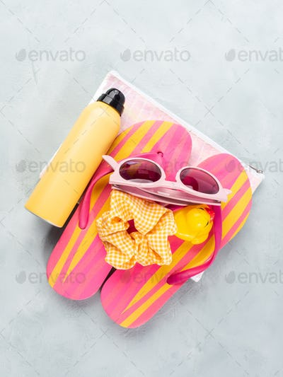 Summer beach, sea vacation accessories with pink flip flops, sun protection and sunglasses on stone