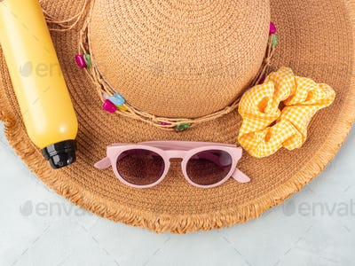 Summer lady straw hat, yellow sun protection spray and sunglasses on turquoise stone background.