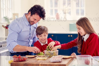 Father Helping Children Wearing School Uniform To Make Healthy Sandwich For Lunch At Home