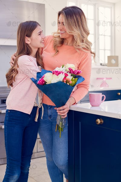 Teenage Daughter Giving Mother Bunch Of Flowers To Celebrate On Mother's Day Or Birthday At Home