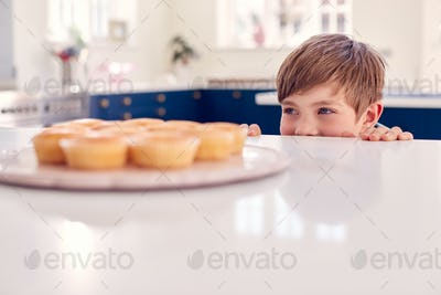 Boy Taking Freshly Baked Homemade Cupcake From Plate In Kitchen At Home