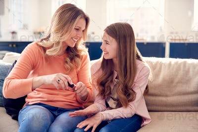 Mother And Daughter Having Fun Sitting On Sofa At Home Doing Nails Together