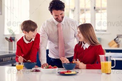 Father Wearing Suit Serving Children In School Uniform Breakfast As He Gets Ready For Work