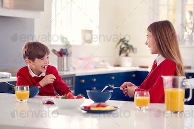 Laughing Brother And Sister Wearing School Uniform In Kitchen