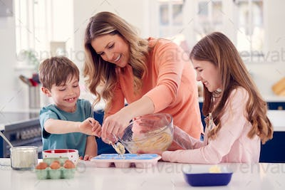 Mother With Two Children In Kitchen At Home Having Fun Baking Cakes Together