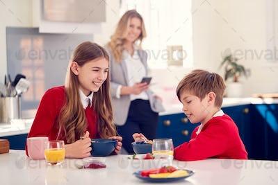 Mother Wearing Business Suit Having Breakfast With Children In School Uniform Before Work