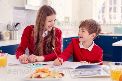 Brother And Sister Wearing School Uniform Doing Homework On Kitchen Counter With Healthy Snacks