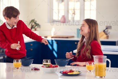 Brother And Sister Wearing School Uniform In Kitchen Have Fun Hanging Spoon From Nose At Breakfast