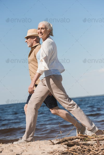 Side view of happy senior couple holding hands and walking on sandy beach