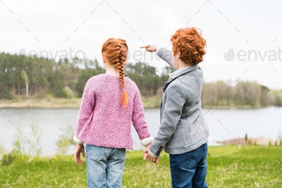 back view of cute redhead siblings holding hands and pointing away with finger outdoors