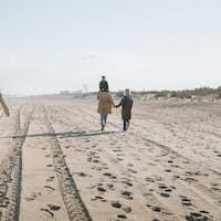 big multigenerational family walking together on seashore