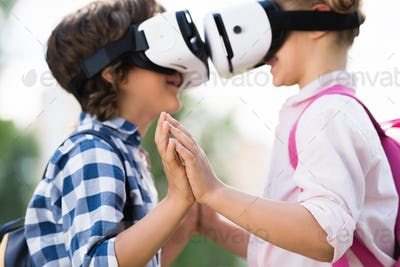 side view of smiling boy and girl in virtual reality headsets holding hands together