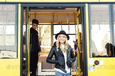 selective focus of smiling woman walking out city bus
