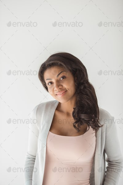 portrait of smiling young african american woman isolated on white