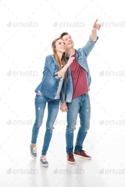 happy young couple holding hands and pointing away with finger isolated on white