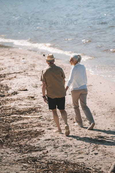 Back view of senior couple holding hands and walking on sandy beach