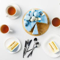top view of sliced cake on chopping board with tea cups and plates isolated on white