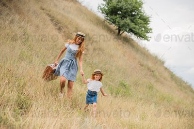 happy little girl and young woman with suitcase holding hands and walking on grassy hill