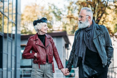 portrait of fashionable senior couple holding hands and looking at each other on street