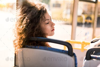 attractive young woman with curly hair sleeping in city bus