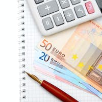 Pen, banknotes and the calculator on a notebook.