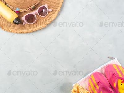 Summer sea vacation accessories. Straw hat, flip flops, sun spray, sunglasses on stone background.
