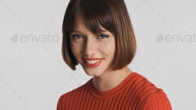 Pretty girl with bob hair and red lips look charming over white background. Cute expression