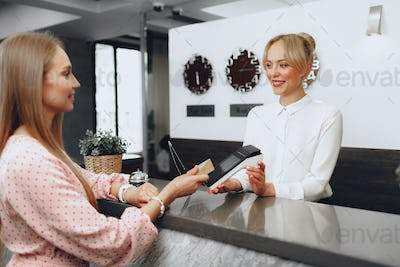 Young beautiful woman hotel guest paying for her stay with credit card at front desk
