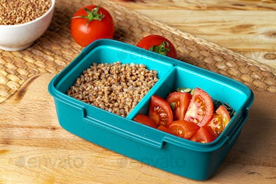 Blue lunch box with buckwheat and tomatoes