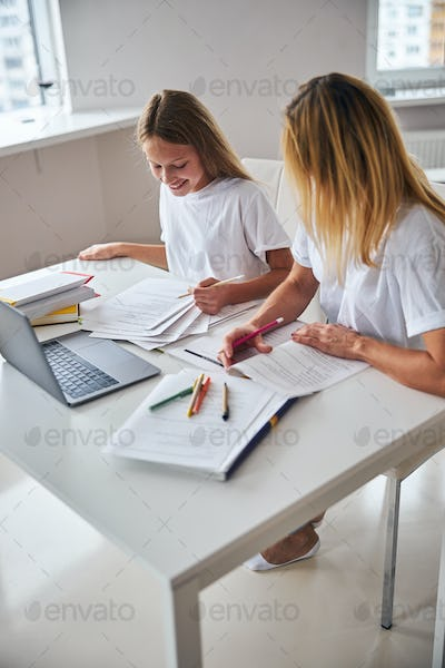 Woman aiding a teenager with her English exercises