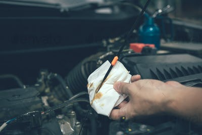 Car mechanic is checking the engine oil of the car using a steel and cleaner by tissue.