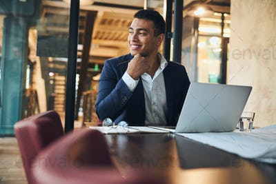 Cheerful office employee sitting at his laptop