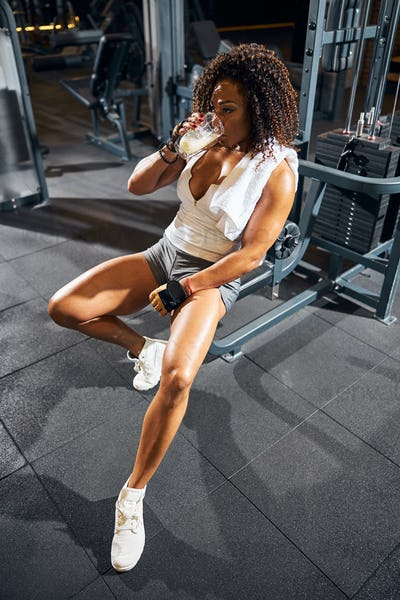 Sportswoman with a beverage sitting at the gym