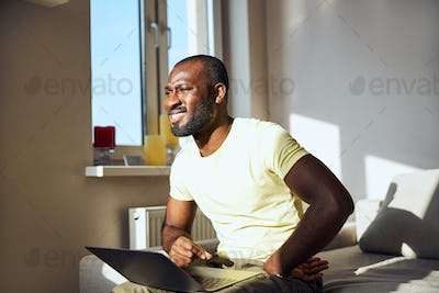Afro-American male is squinting from the sun
