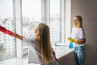 Girl helping her mother wash the windowpane