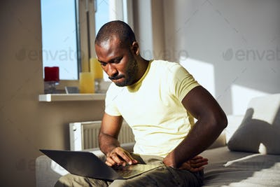 Anxious worker sitting on a bed edge with a computer