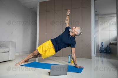 Healthy man carrying out a side plank during workout