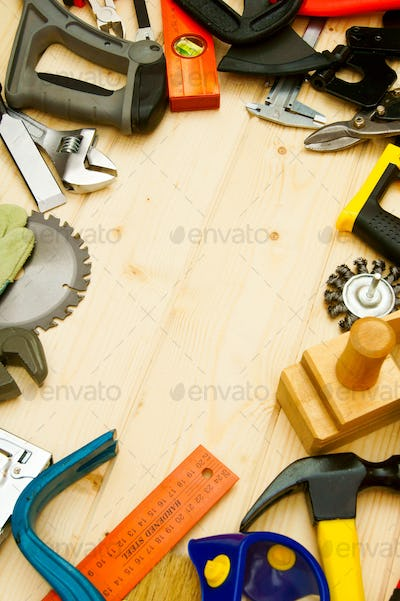The different working tools (stapler, mallet, saw and others) on a wooden background.